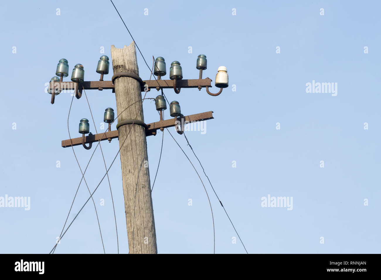 Old electric wooden pole with glass and ceramic insulators and