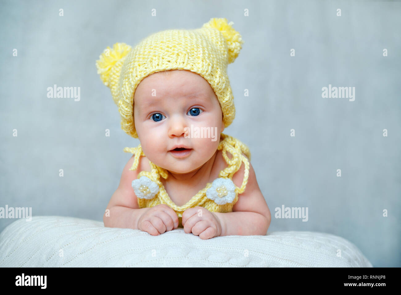 ce5acab52 Portrait of a cute newborn baby girl in yellow knitted hat Stock ...