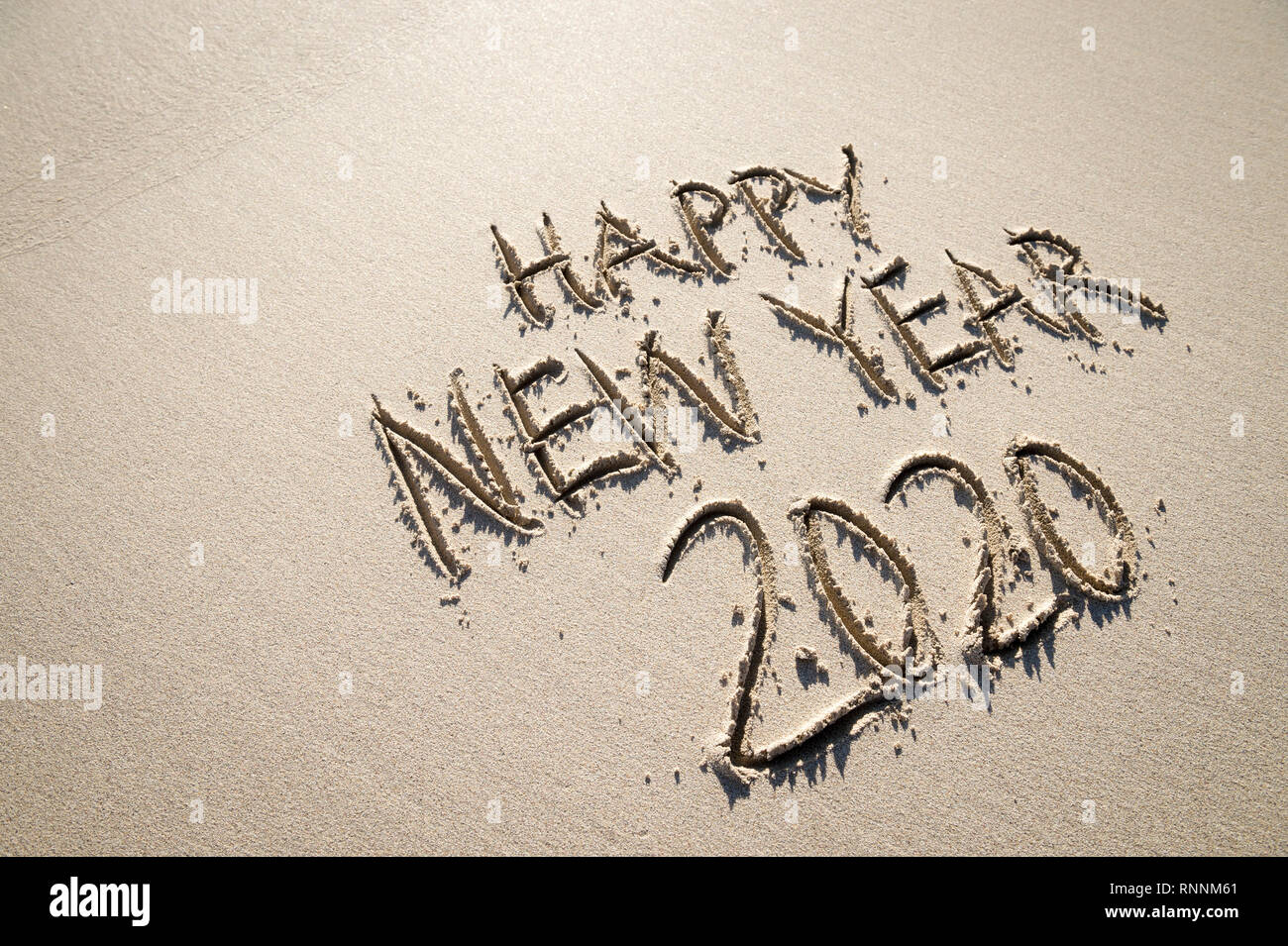 Happy New Year 2020 message handwritten in raised textured letters on a sand beach with smooth copy space Stock Photo