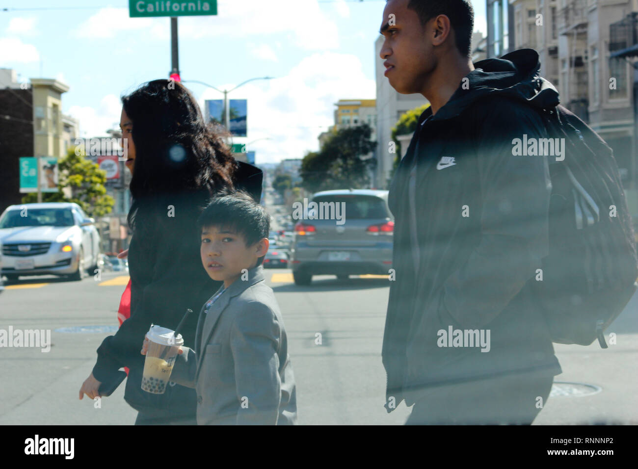 A young boy turns to the camera as he crosses the street in the city of San Francisco, CA. - Stock Image