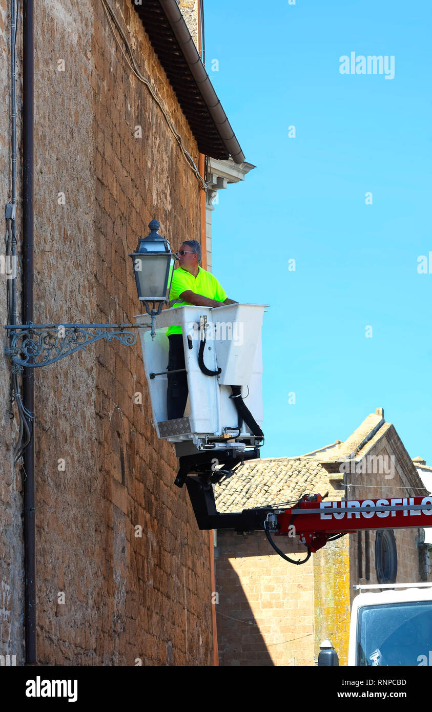 utility repairman; bucket truck; old street lamp; lantern; neon green shirt, stone buiding; working; occupation; Europe; Orvieto; Italy; summer; verti - Stock Image