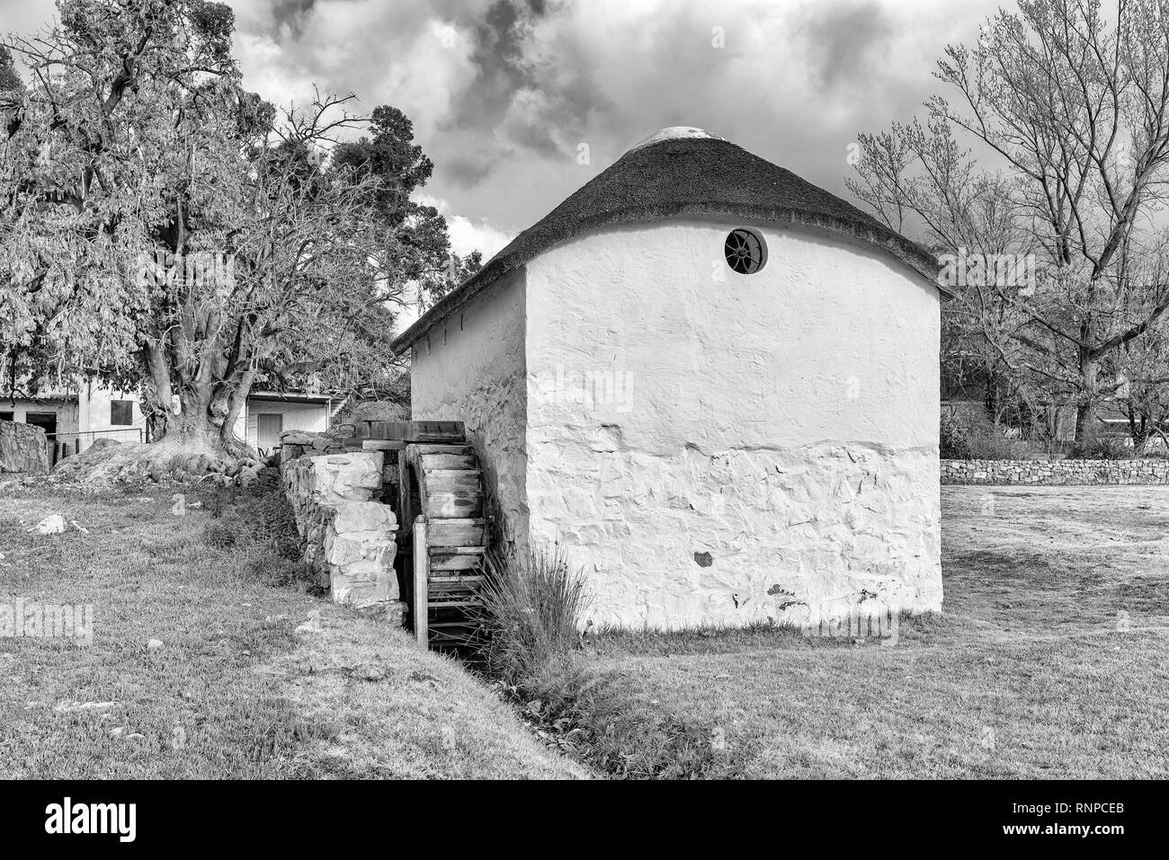 KROMRIVIER, SOUTH AFRICA, AUGUST 25, 2018: The historic water mill at Kromrivier Cederberg Park, a holiday resort in the Cederberg Mountains. Monochro - Stock Image