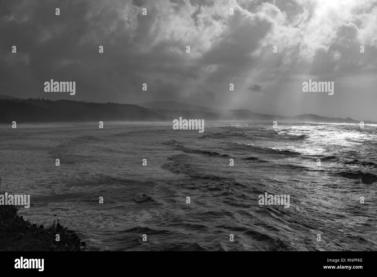 The dramatic and rugged Orgeon coastline, shot in black and white to add drama, shafts of light coming through the breaks in the clouds - Stock Image