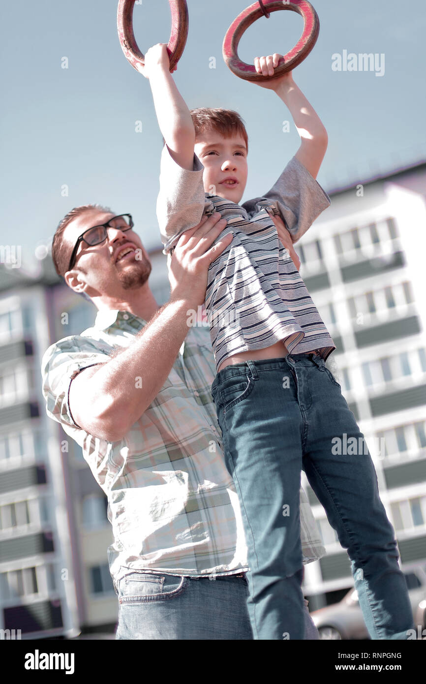 father helps his son to catch up on the bar - Stock Image