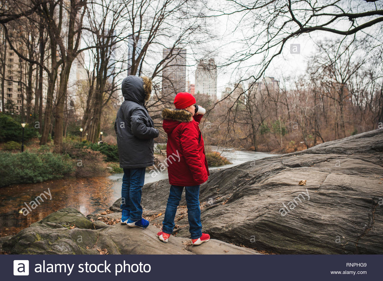 Two boys in parkas taking in the sights of Central Park, New York City. - Stock Image