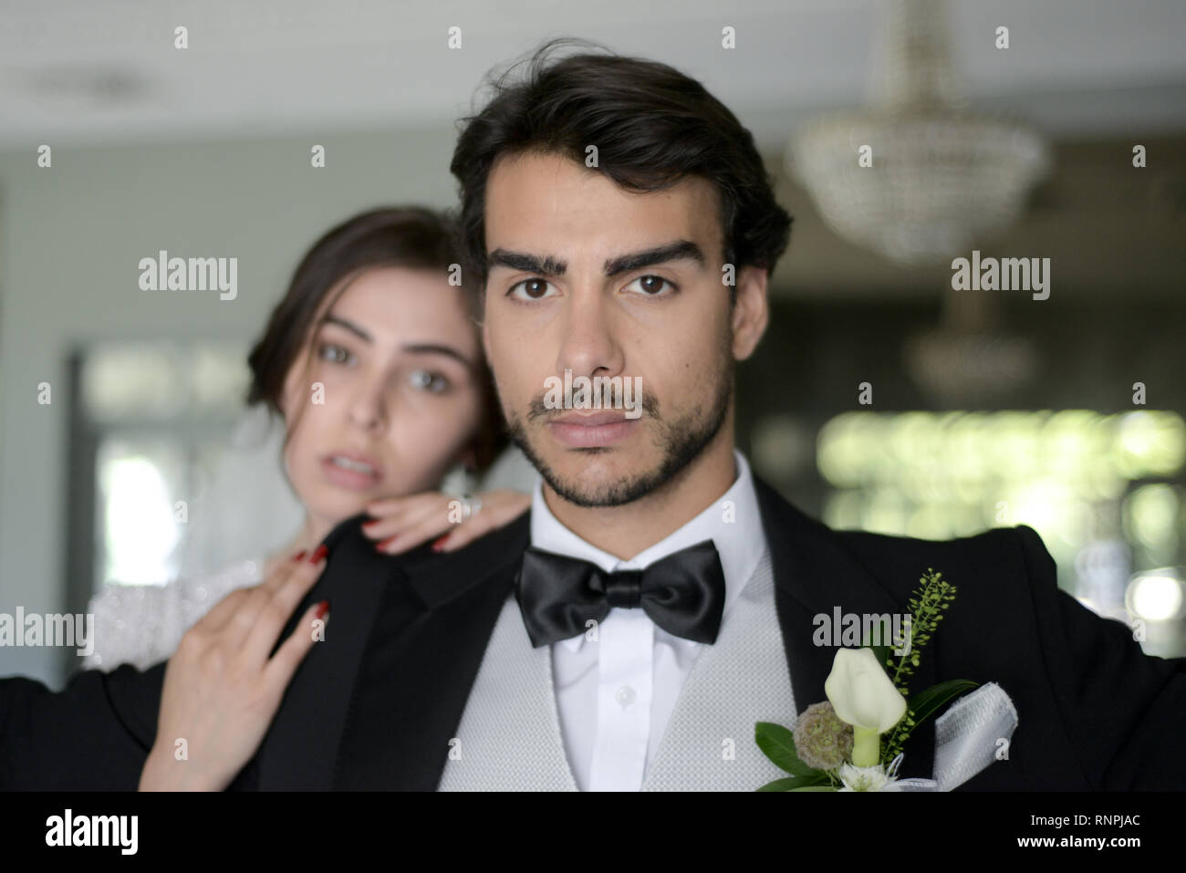A young pensive couple have a traditional English White Wedding, they are both dark haired and good looking but seem unhappy - Stock Image