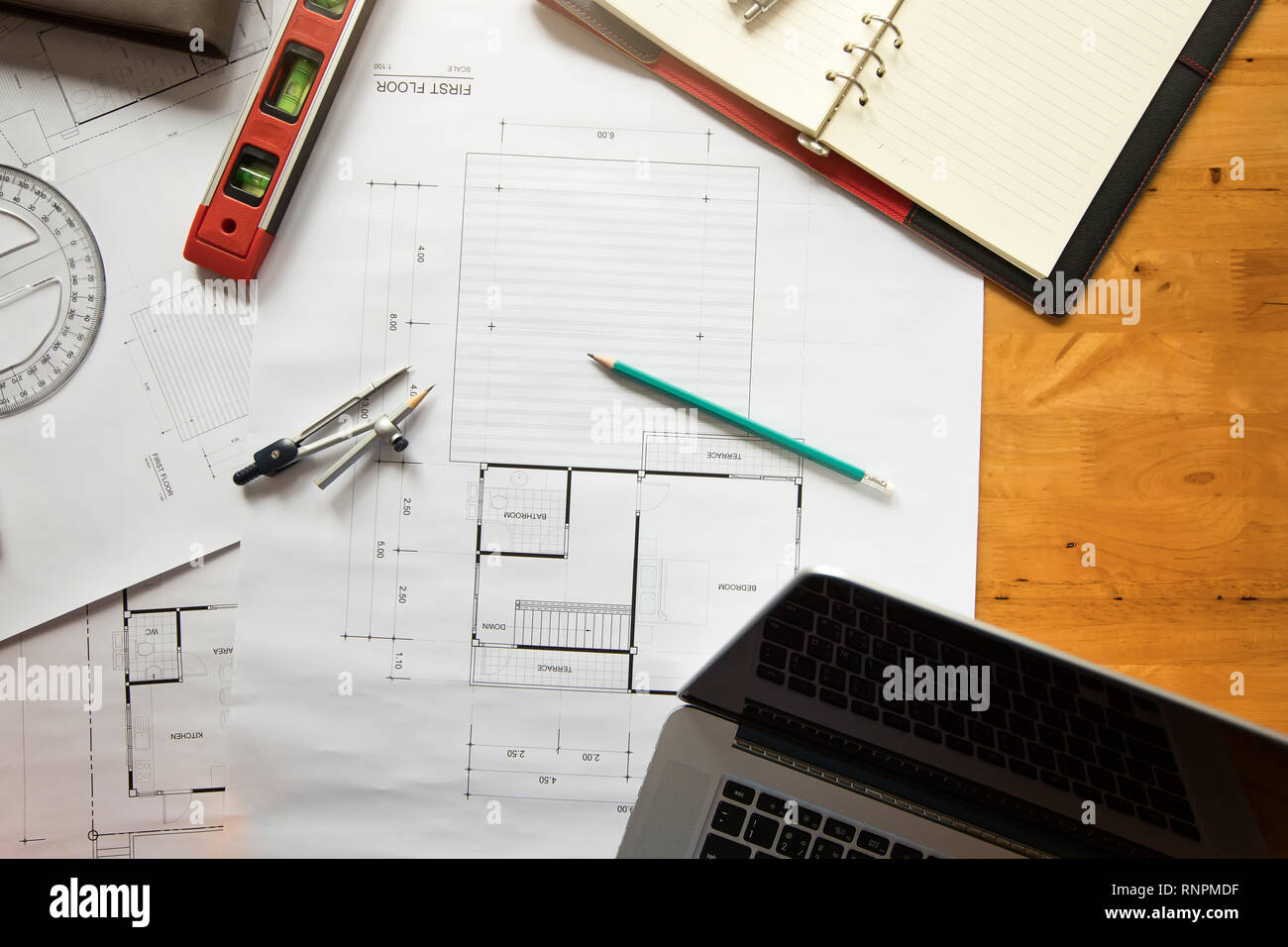 Top view of measurement tool with helmet and laptop on blueprint, architectural concept - Stock Image
