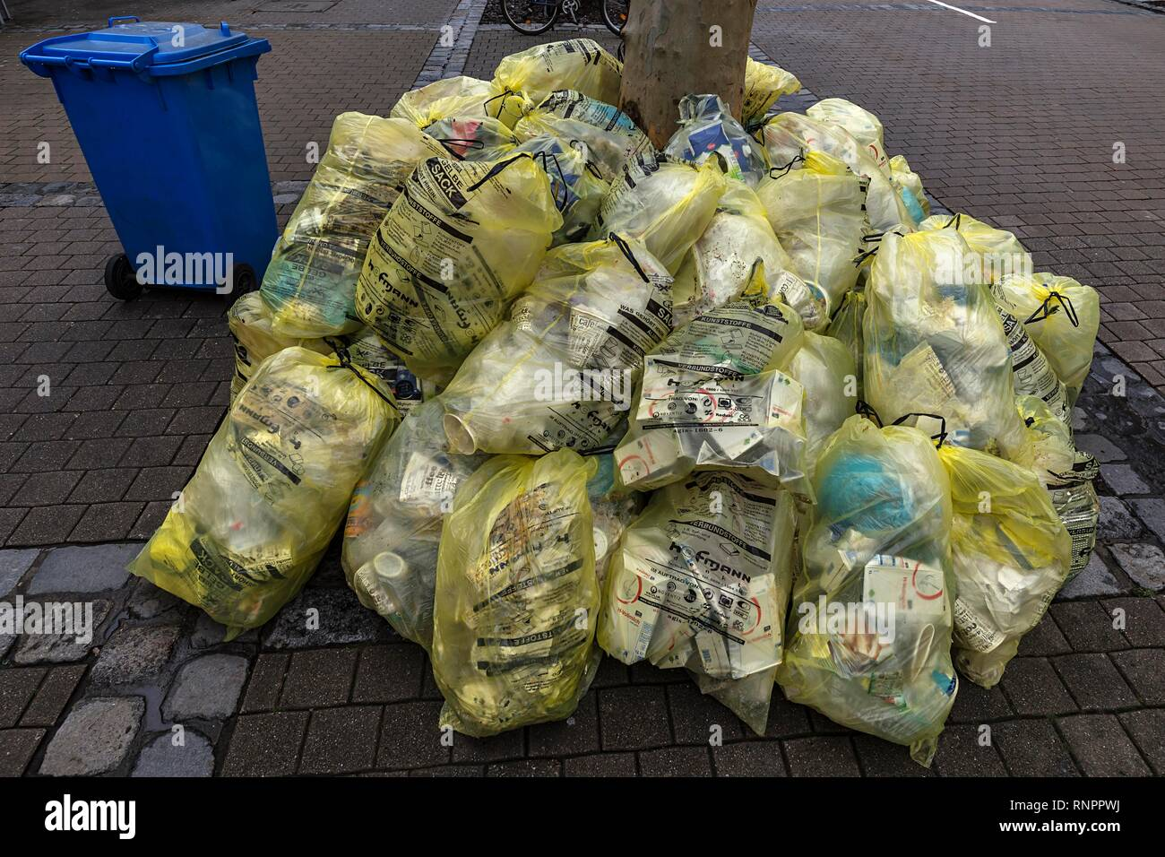 Stacked yellow sacks for waste disposal in the pedestrian zone, Erlangen, Middle Franconia, Bavaria, Germany, Europe - Stock Image