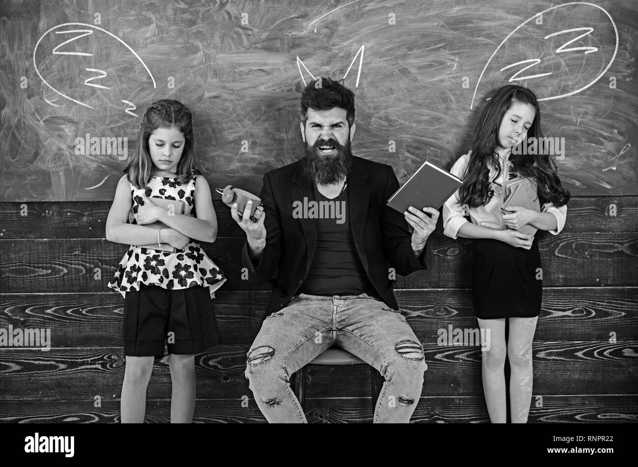 Monster teacher shout at sleepy pupils. Angry man with alarm clock and book. Little girls students tired of study in school. Tutor and schoolgirls - Stock Image