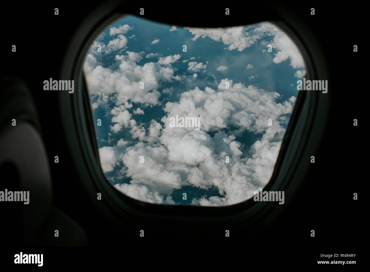 Beautiful white clouds and blue sea water viewed from a plane window during flight. Stock Photo