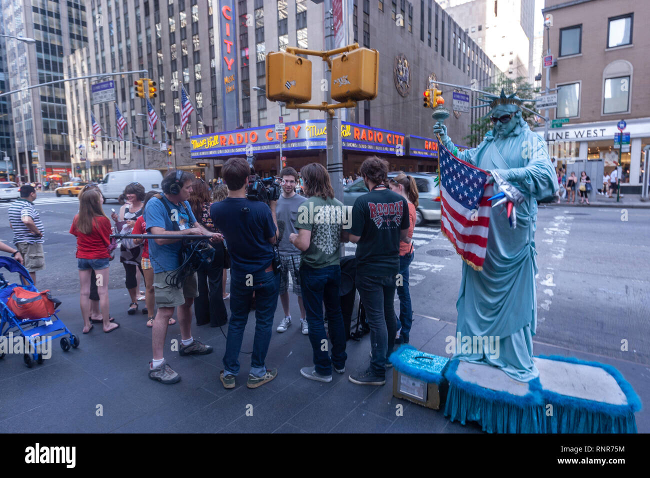 Cameraman interviewing and a mime street performer depicting the Statue of Liberty in New York City Times Square, New York City, USA Stock Photo