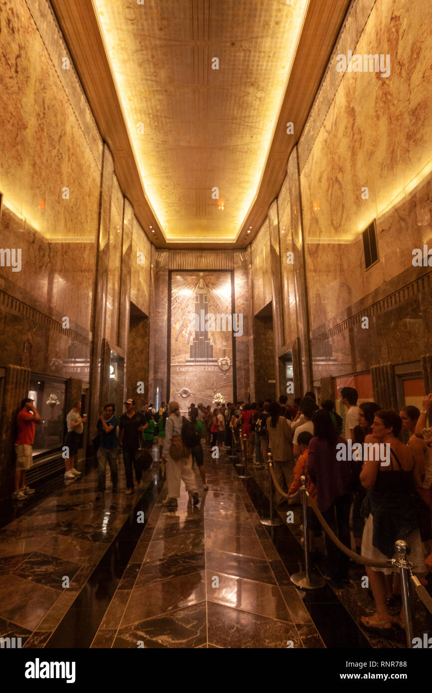 Cue of tourists in Empire State Building lobby and elevators Art Deco skyscraper in Midtown Manhattan,, New York City, USA Stock Photo