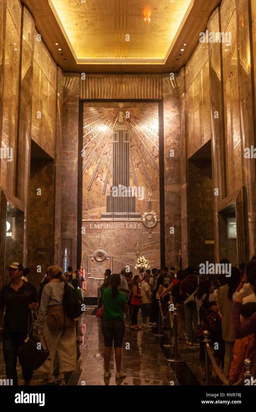 Cue of tourists in Empire State Building lobby and elevators Art Deco skyscraper in Midtown Manhattan,, New York City, USA - Stock Image