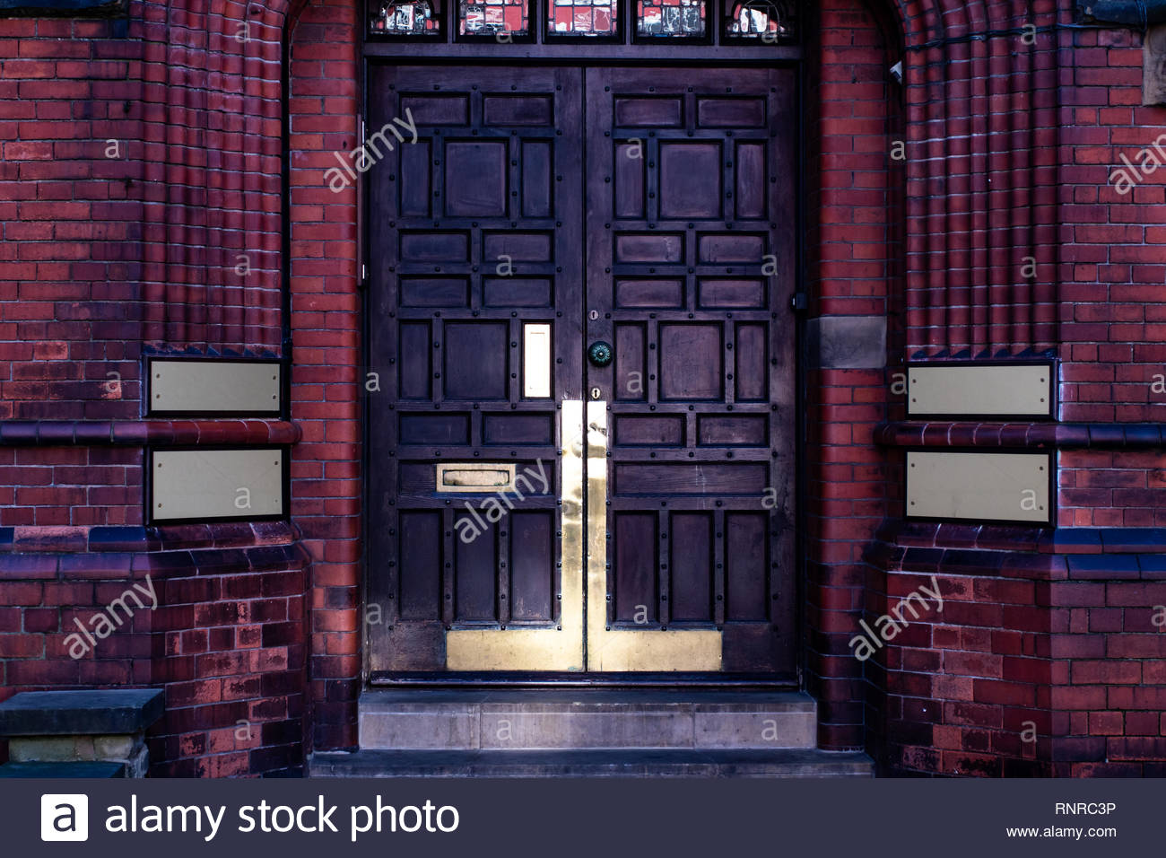 Old wooden doors with 4 blank golden plaques at the side on a brick wall. Stock Photo