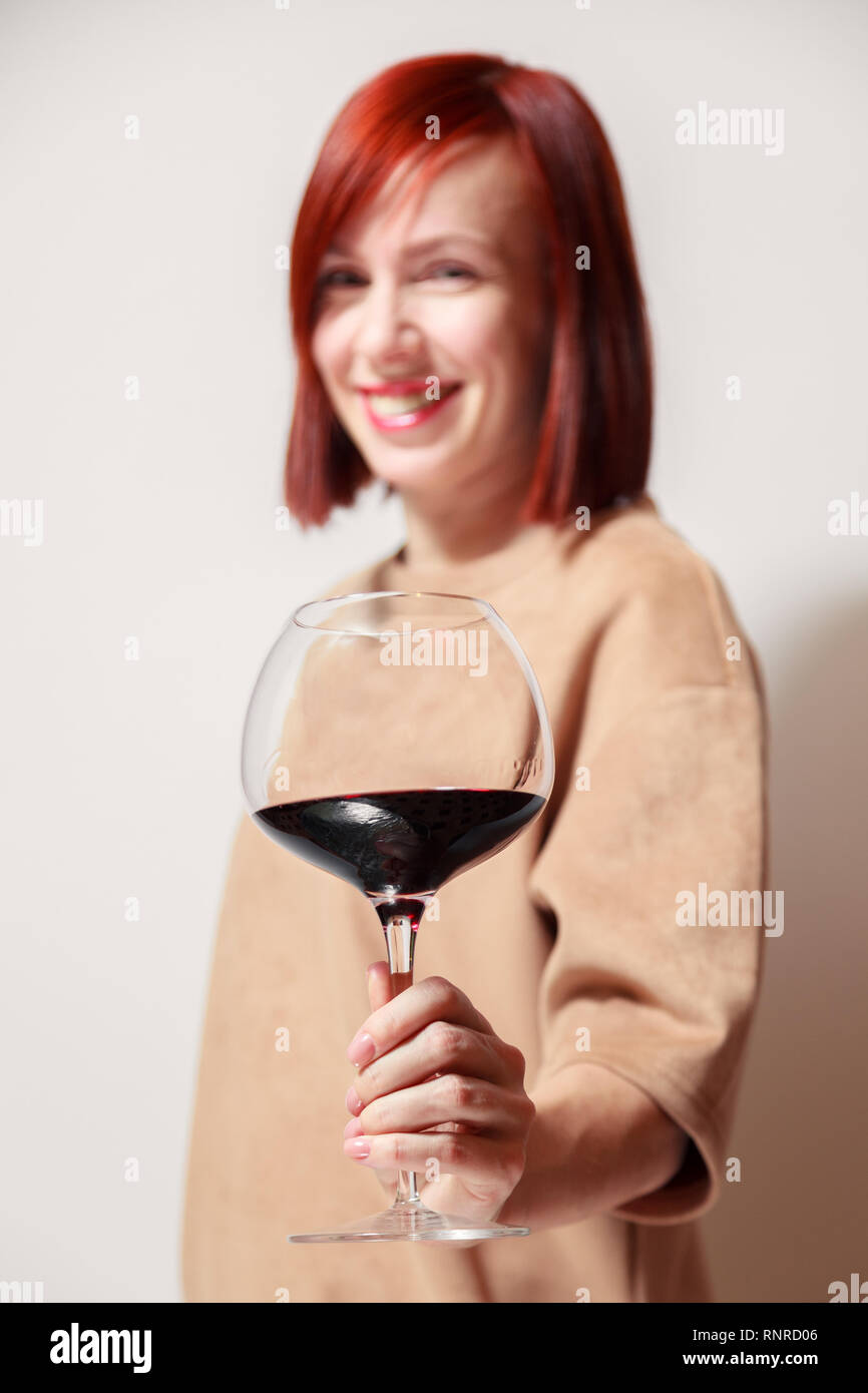 Young beautiful redhaired girl sommelier smiling and holding glass of red wine at professional blind tasting sommelier competition. Concept alcoholism Stock Photo