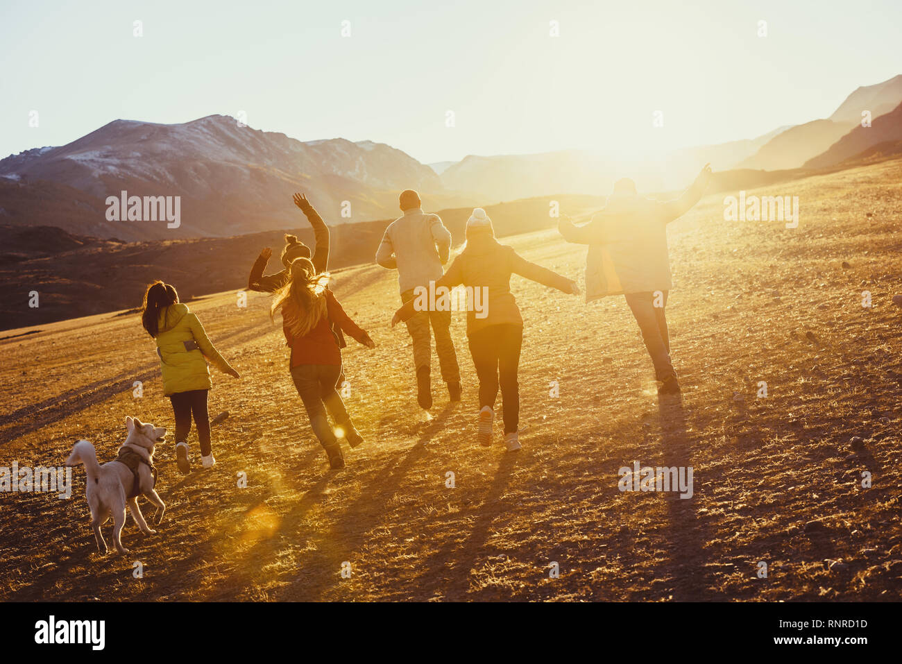 Big group of happy friends run and jump at sunset field against mountains and sun Stock Photo