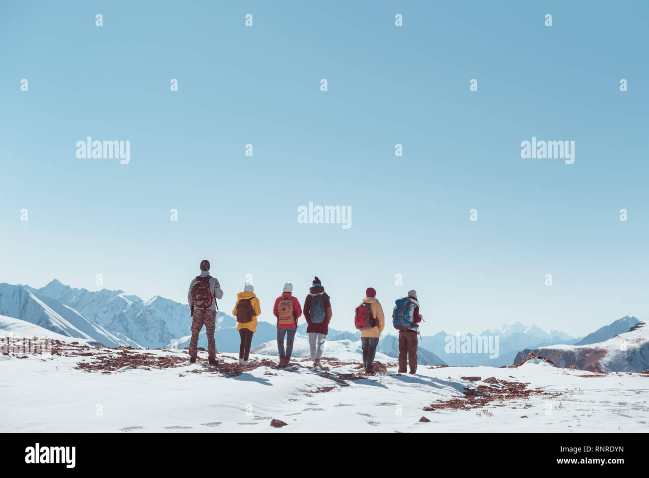 Big group of hikers or tourists or friends stands on mountain pass or top and looks at mountains. Space for text Stock Photo