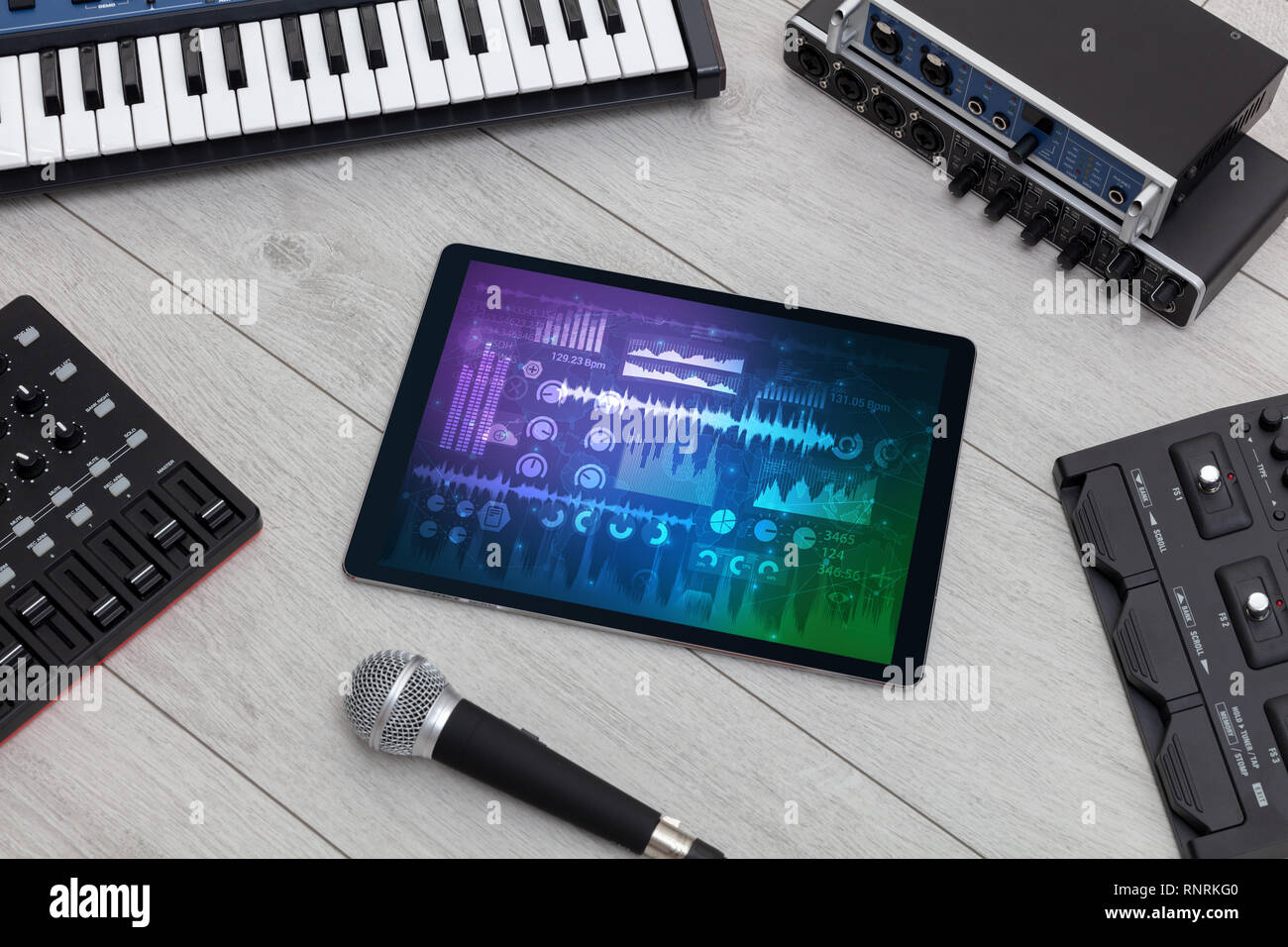 Electronic music instruments, microphone, piano, consoles and tablet with reports concept  - Stock Image