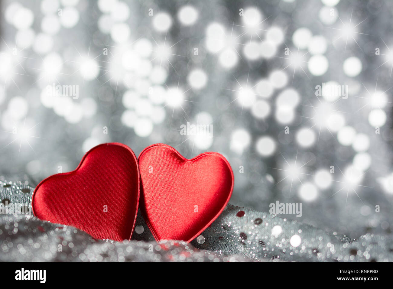 Two red hearts on silver fabric with sequins - silver background with stars and spots bokeh - Stock Image