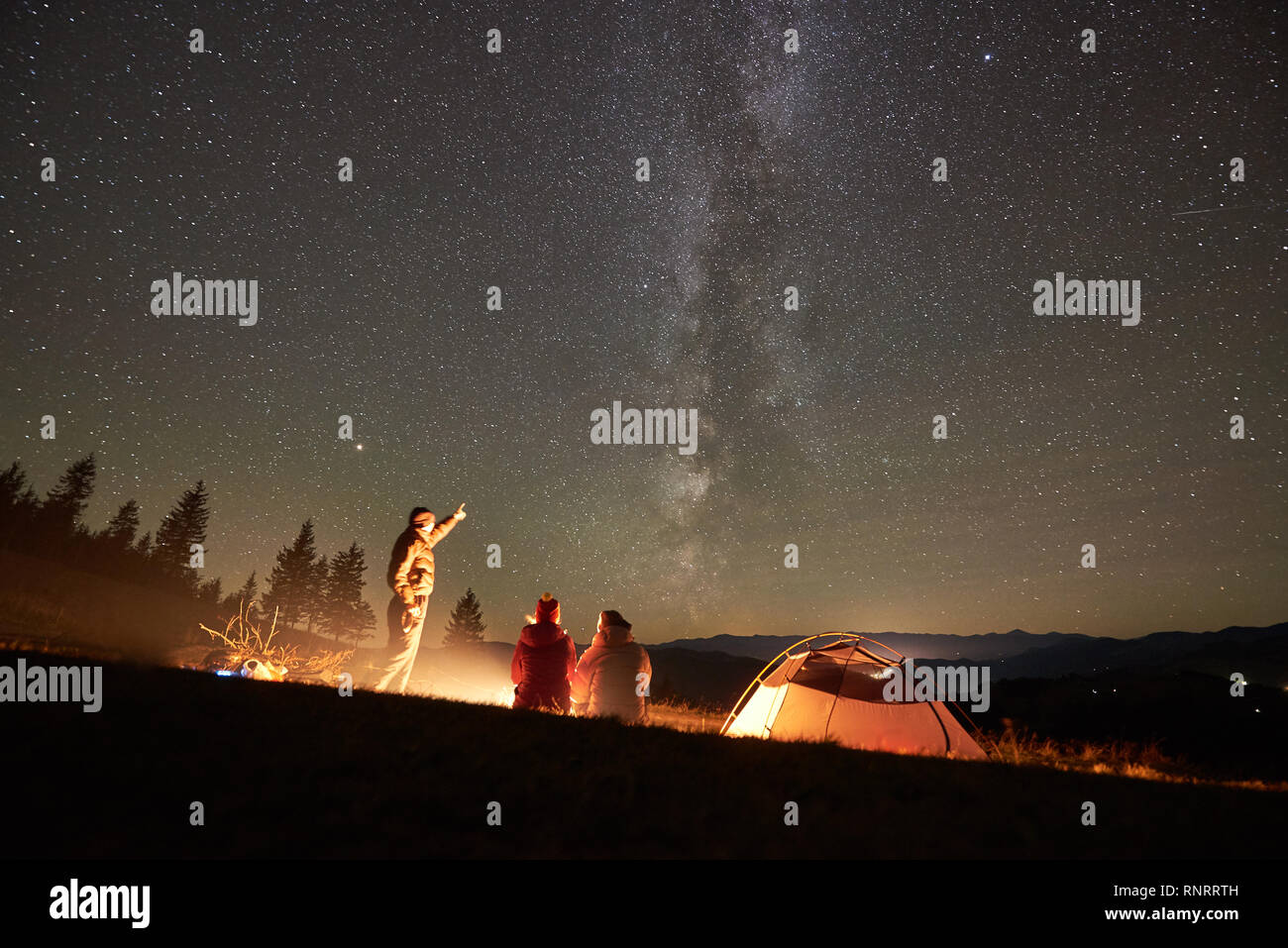 Happy friends hikers having a rest together around campfire beside camp and tourist tent at night in the mountains. Man pointing at incredibly beautiful night starry sky full of stars and Milky way. Stock Photo