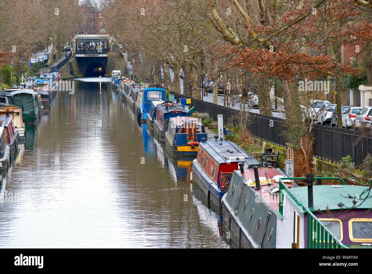LONDON LITTLE VENICE CANAL BOATS ON THE WATER LOOKING TOWARDS A TUNNEL AND CAFE - Stock Image