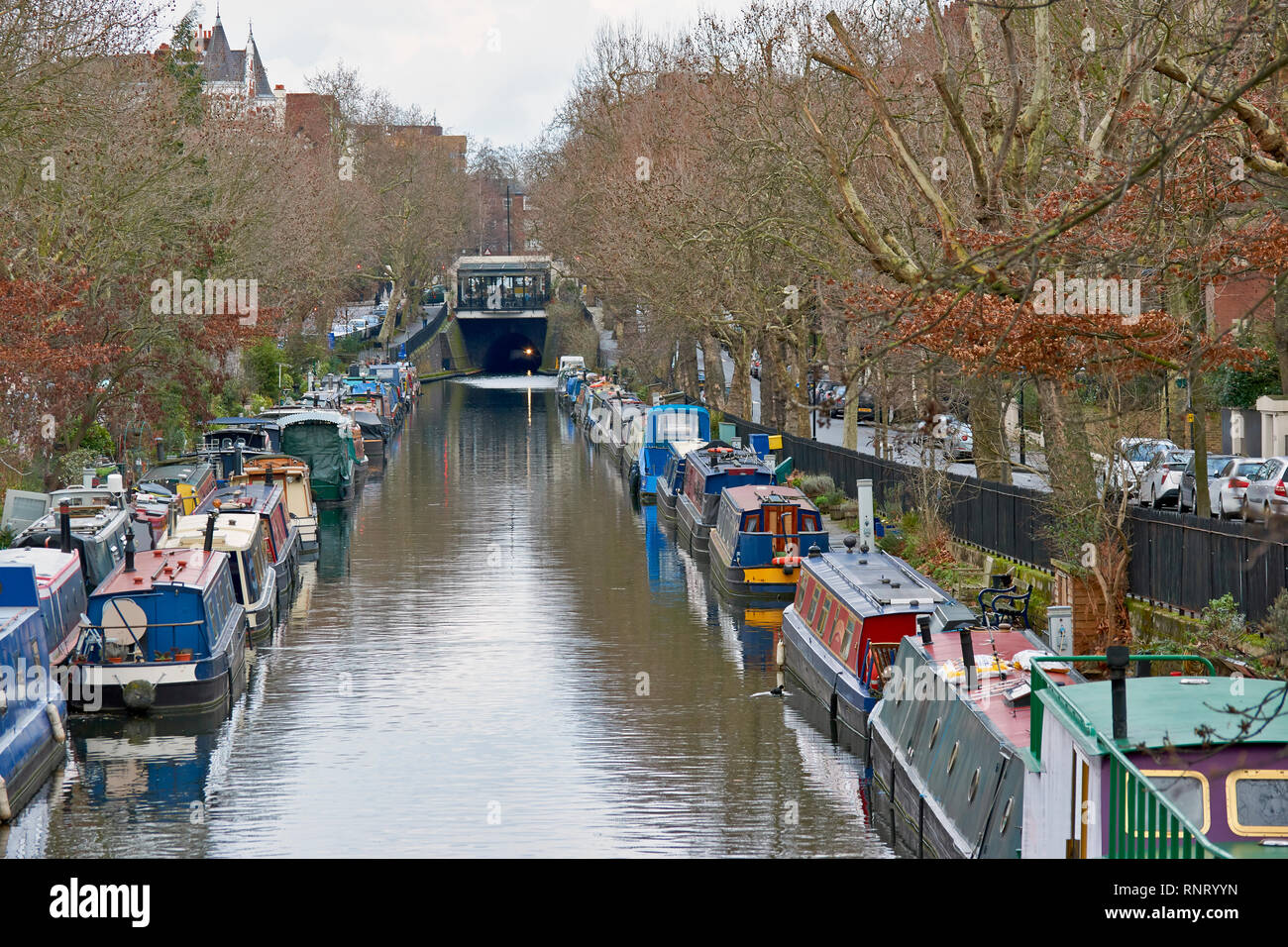 LONDON LITTLE VENICE CANAL BOATS ON THE WATER LOOKING TOWARDS THE TUNNEL AND CAFE - Stock Image