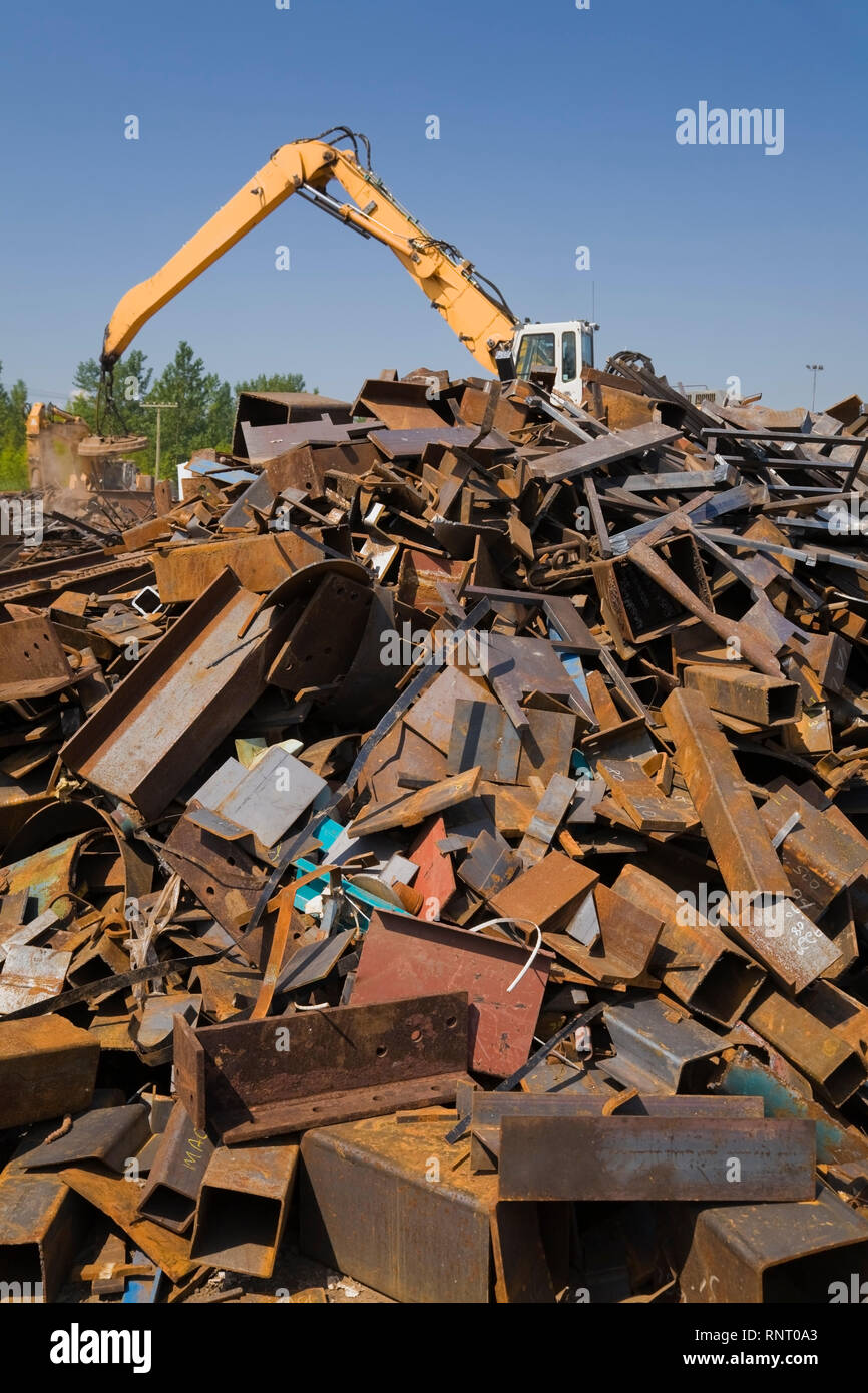 Material handler fitted with a magnet used to move and sort through a pile of discarded ferrous metal at a scrap metal recycling yard - Stock Image