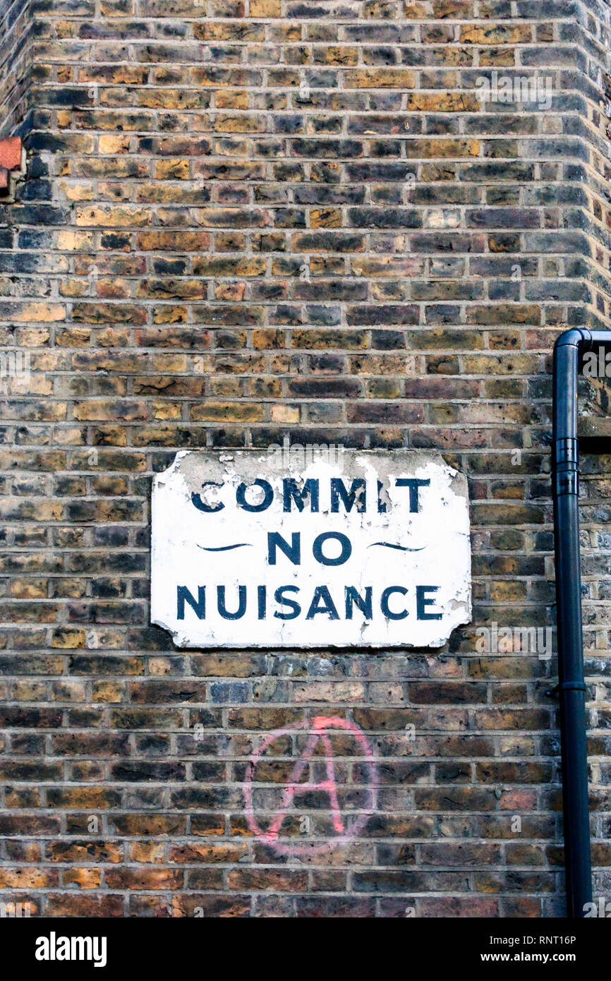 An old sign reading 'Commit No Nuisance', below it a red-painted anarchy sign, on the brick wall of a tenement block in Southwark, London, UK - Stock Image