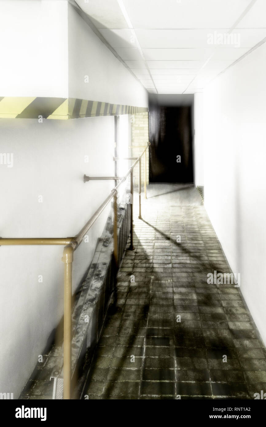 A bright light emanating from the end of an industrial corridor with a black door, motion blurred Stock Photo