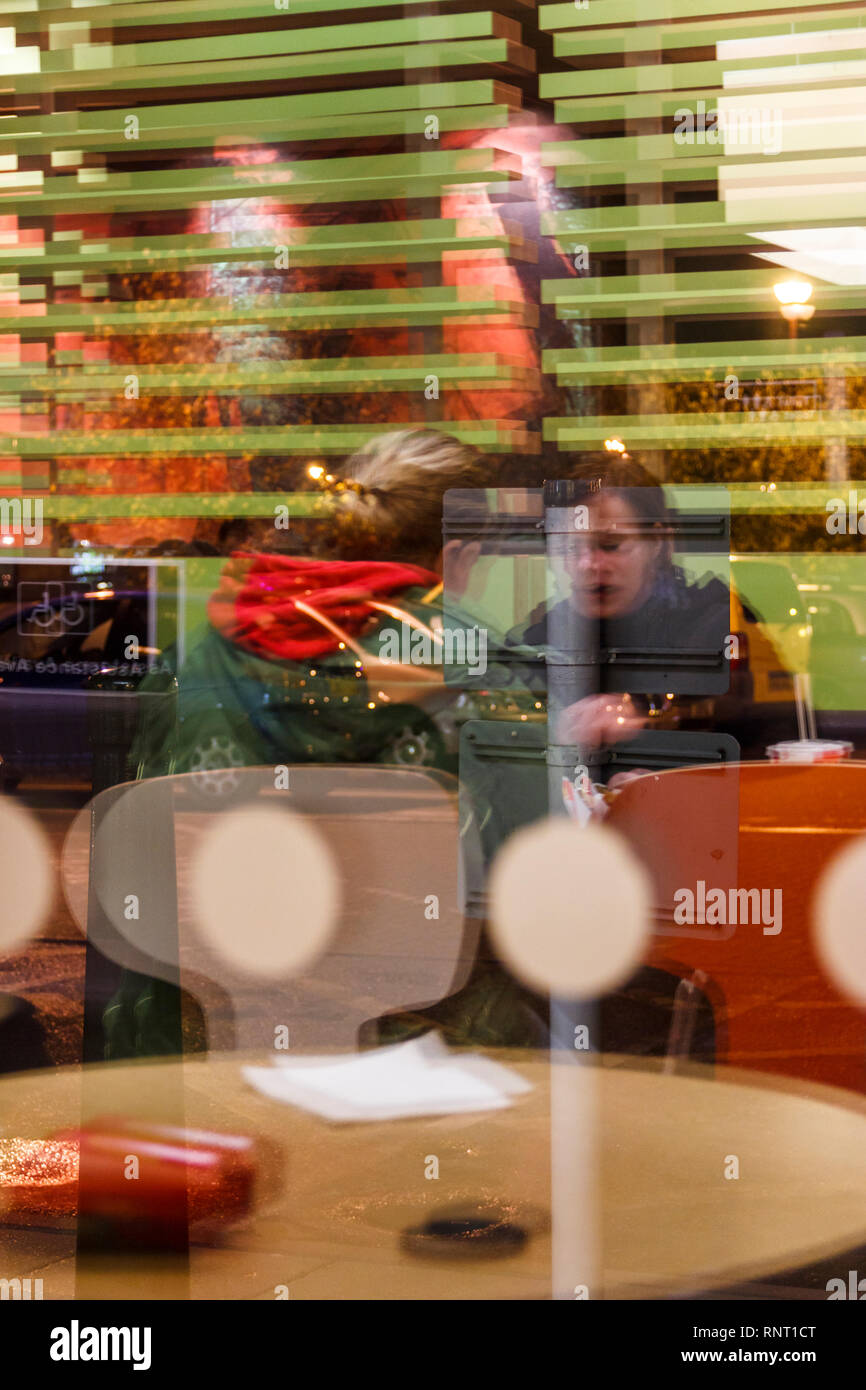 Blurred image of a man and woman sitting in a fast food restaurant, seen through the window at night - Stock Image