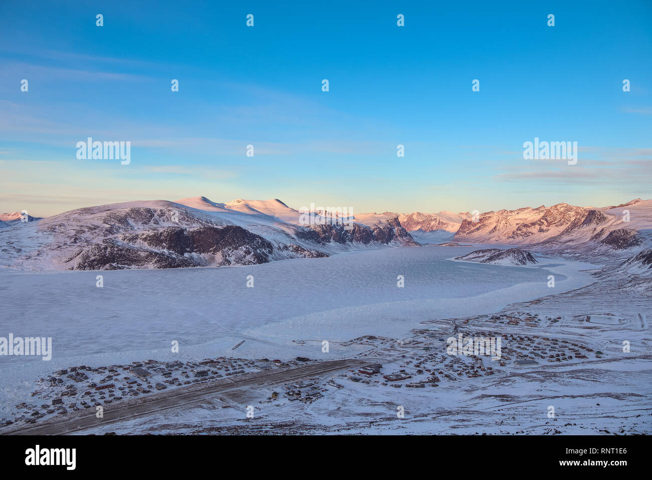 Overlooking the town of Pangnirting. This is the entire town visible soutth (left) to north during sunset in winter. - Stock Image
