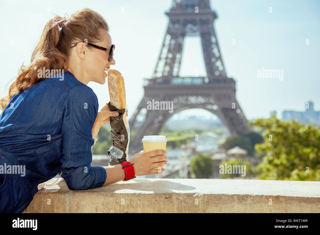smiling elegant traveller woman in blue jeans overall with coffee cup eating baguette having excursion against clear view of the Eiffel Tower in Paris Stock Photo