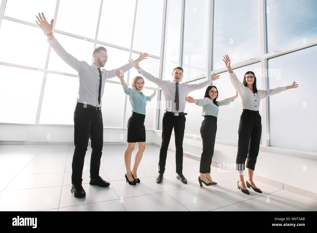 business team standing in spacious new office. - Stock Image