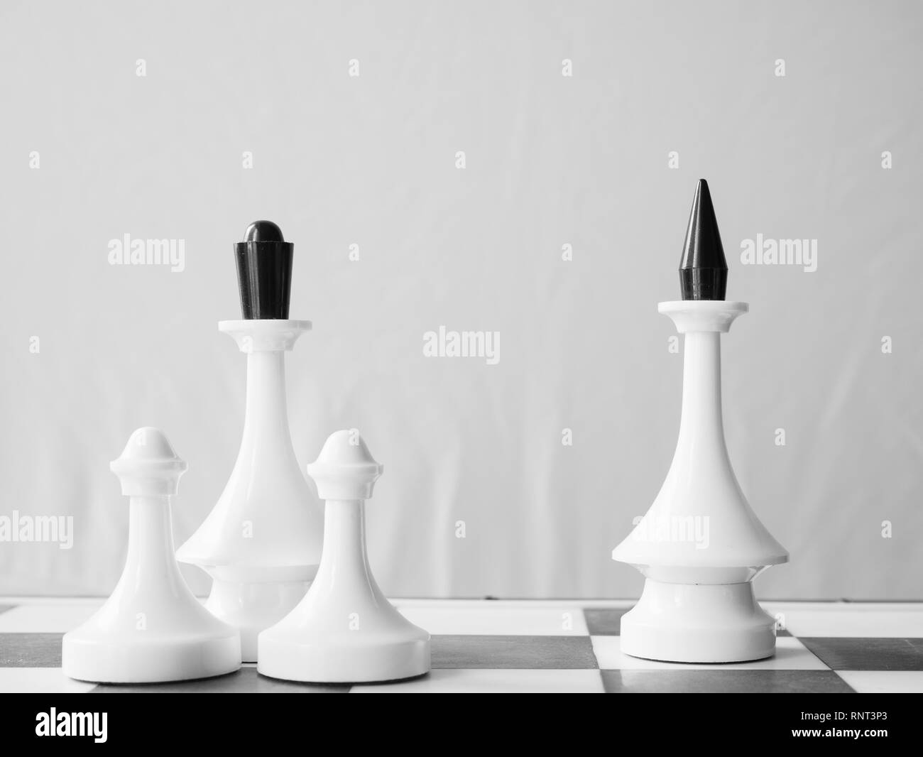 chessman king and queens with few pawns on different parts of shess board. depict family divorce when children stay with mother - Stock Image