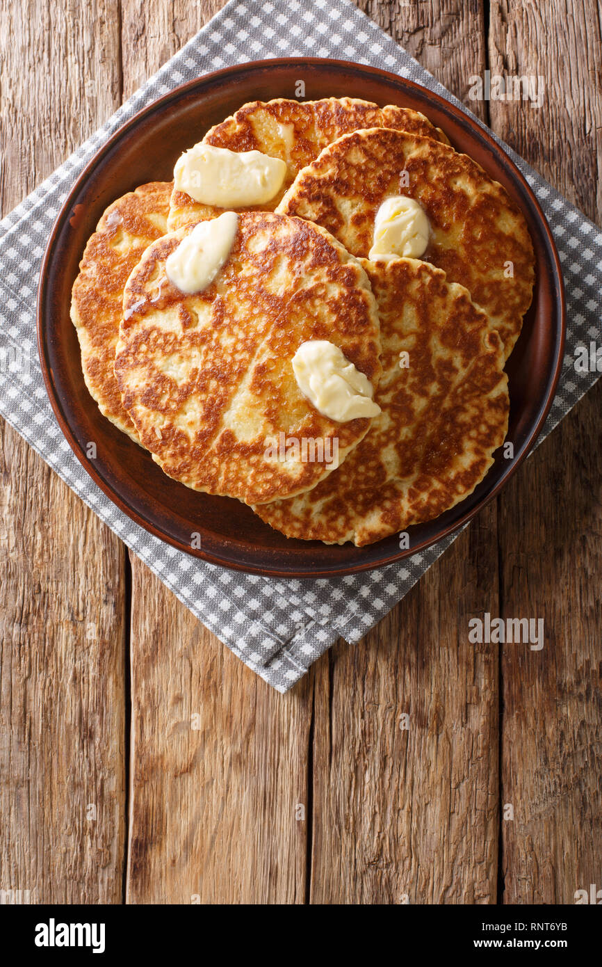 Gorditas de Azucar (Sweet Griddle Cakes) with butter close-up on a plate on the table. Vertical top view from above - Stock Image