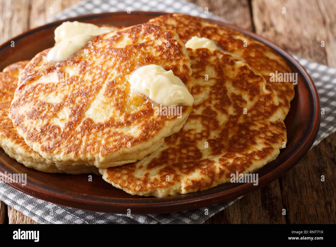 Mexican pancakes Gorditas de Azucar with butter close-up on a plate on the table. horizontal - Stock Image