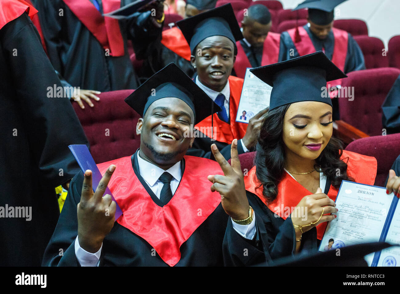 GRODNO, BELARUS - JUNE, 2018: Foreign african medical students in square academic graduation caps and black raincoats during commencement with diploms - Stock Image