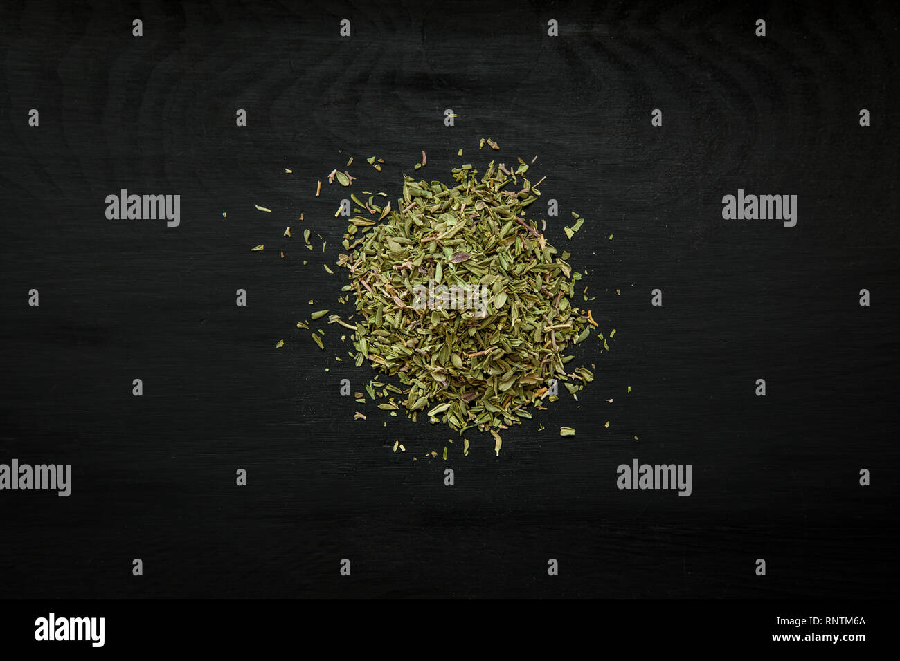 Close-up image of dried thyme on black wood background, view above - Stock Image