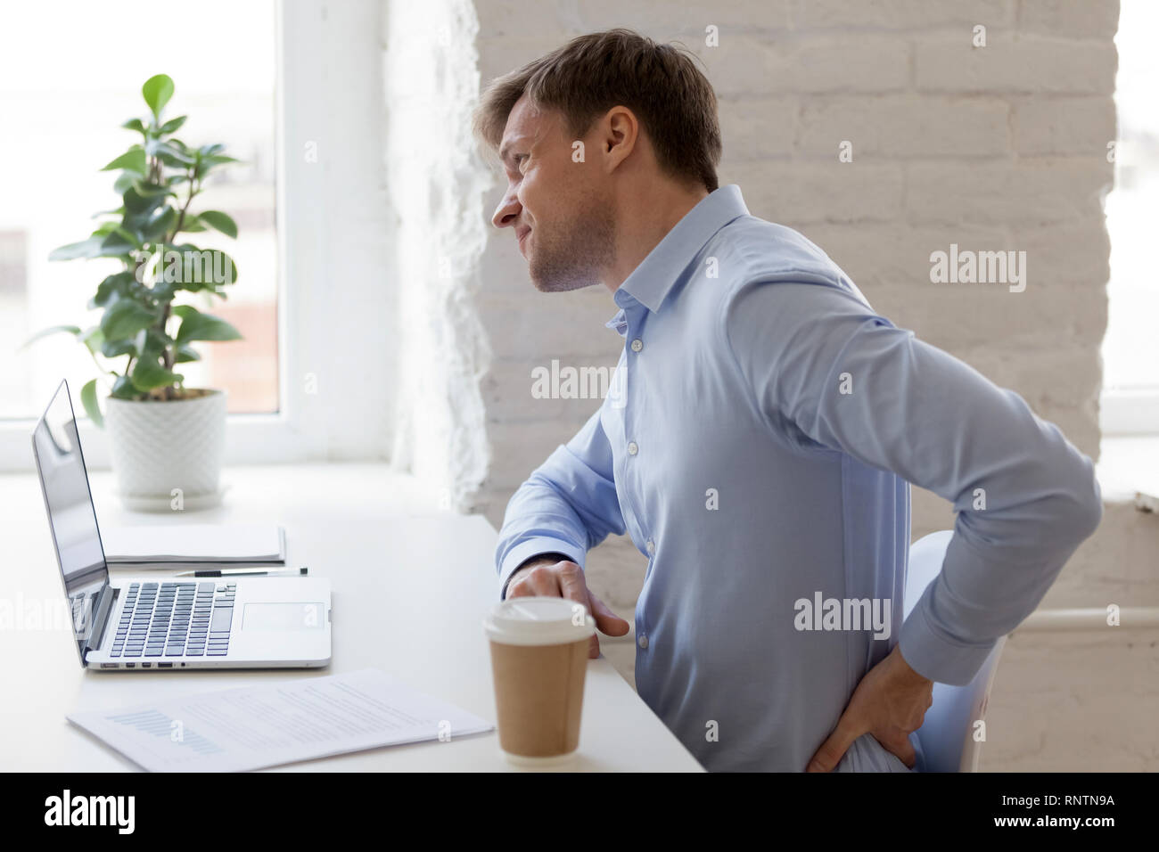 Office worker having strong lower back pain - Stock Image