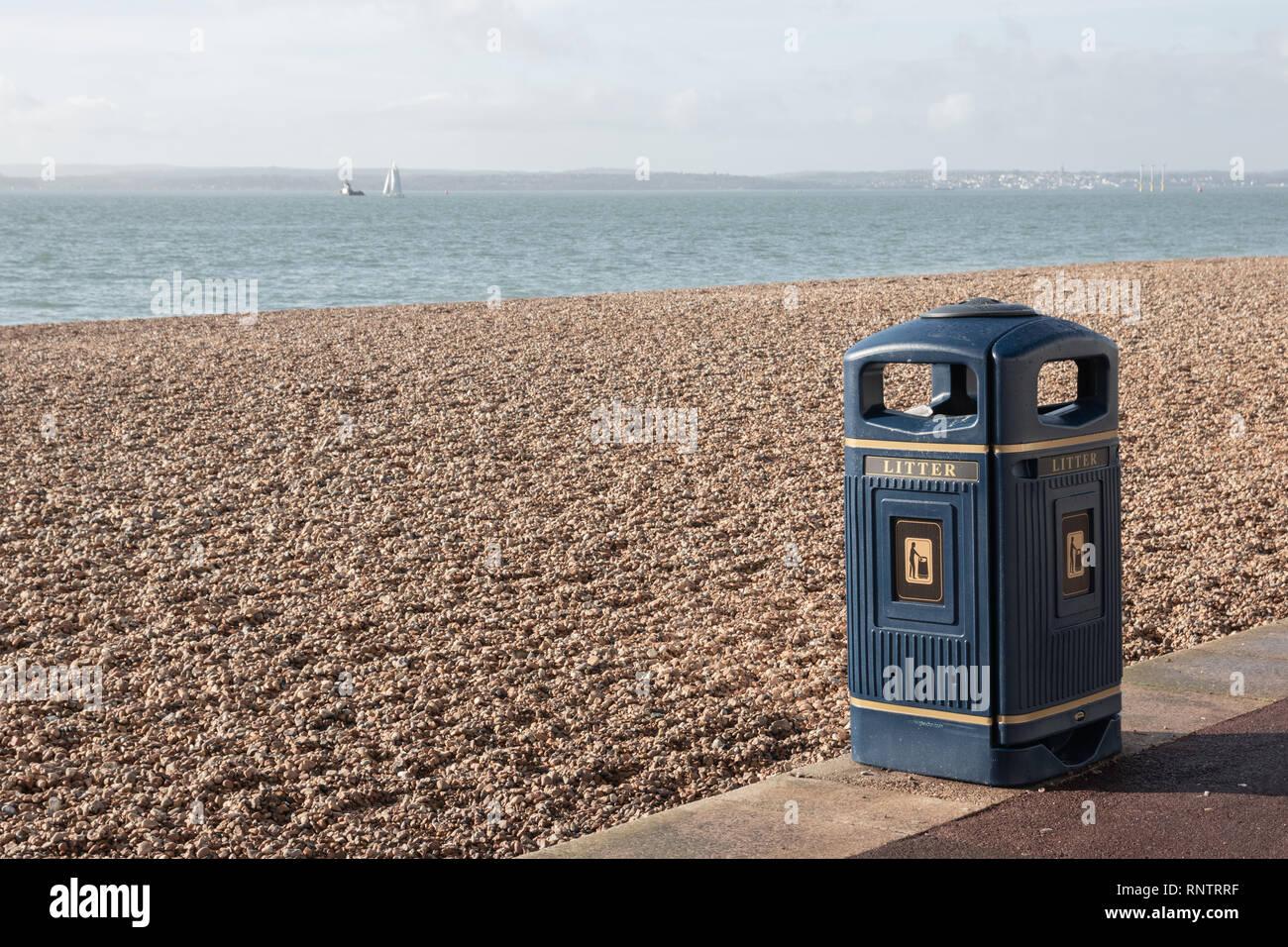 litter bin next to a pebble beach - Stock Image