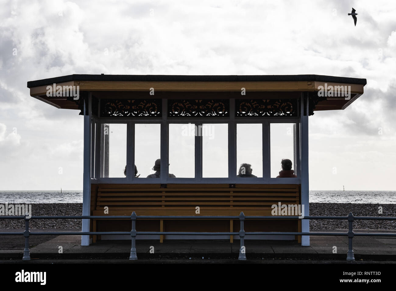 People sat on victorian shelter, Southsea, Portsmouth, Hampshire, UK Stock Photo