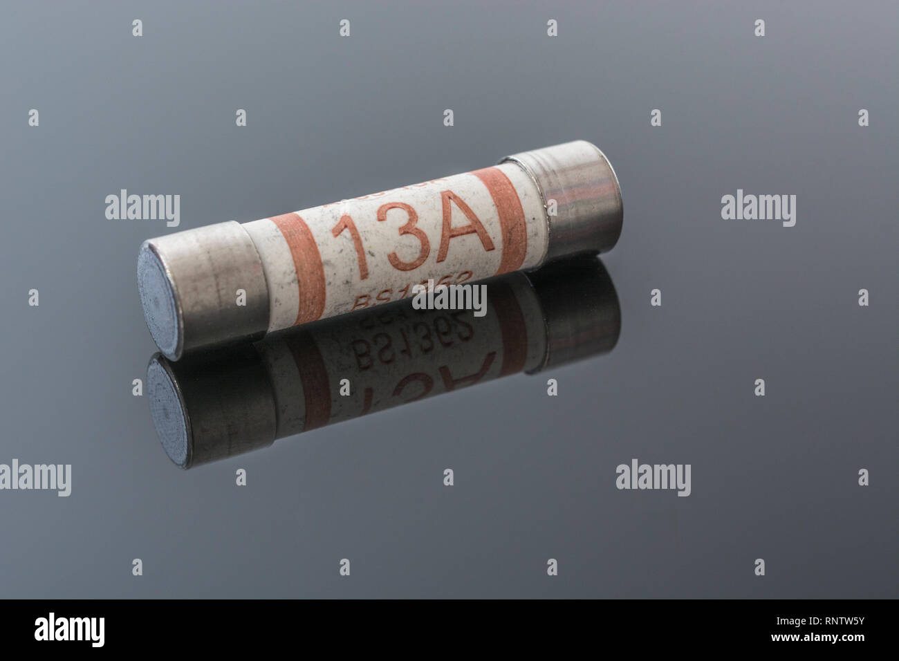 Domestic appliance electrical 13 Amp fuse (Ceramic Cartridge type) on reflective black background. Metaphor electrical safety. 25mm L x 6.3mm D Stock Photo