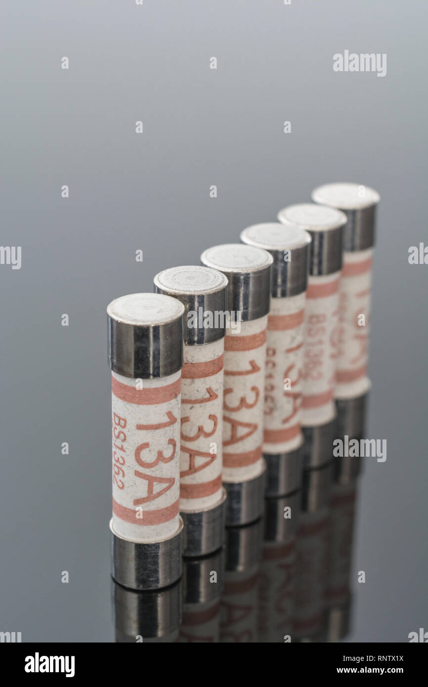 Domestic appliance electrical 13 Amp fuses (Ceramic Cartridge type) on reflective black background. Metaphor electrical safety. 25mm L x 6.3mm D Stock Photo