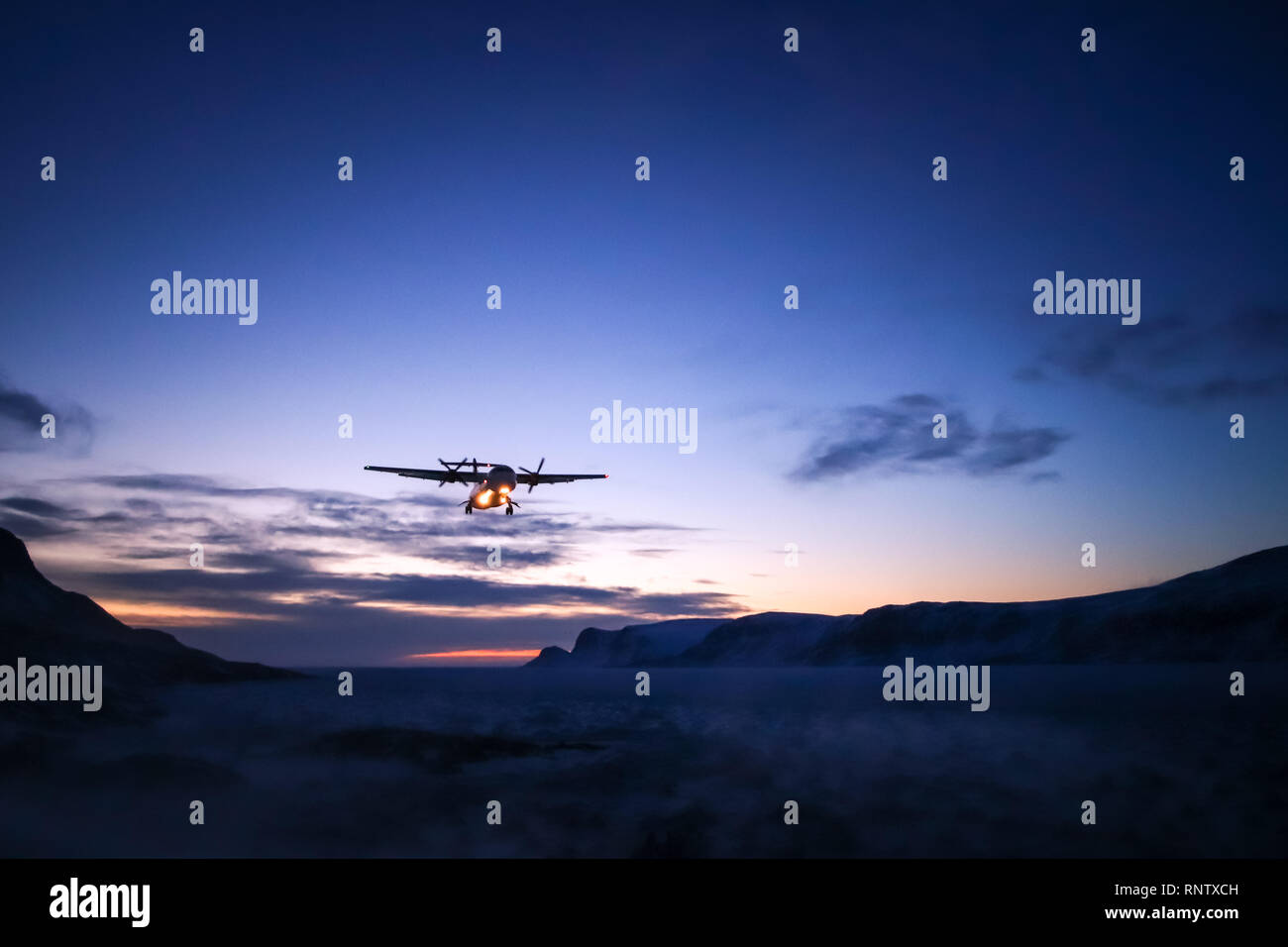 Plane coming into land at Pangnirtung Airport during a winter sunset - Stock Image