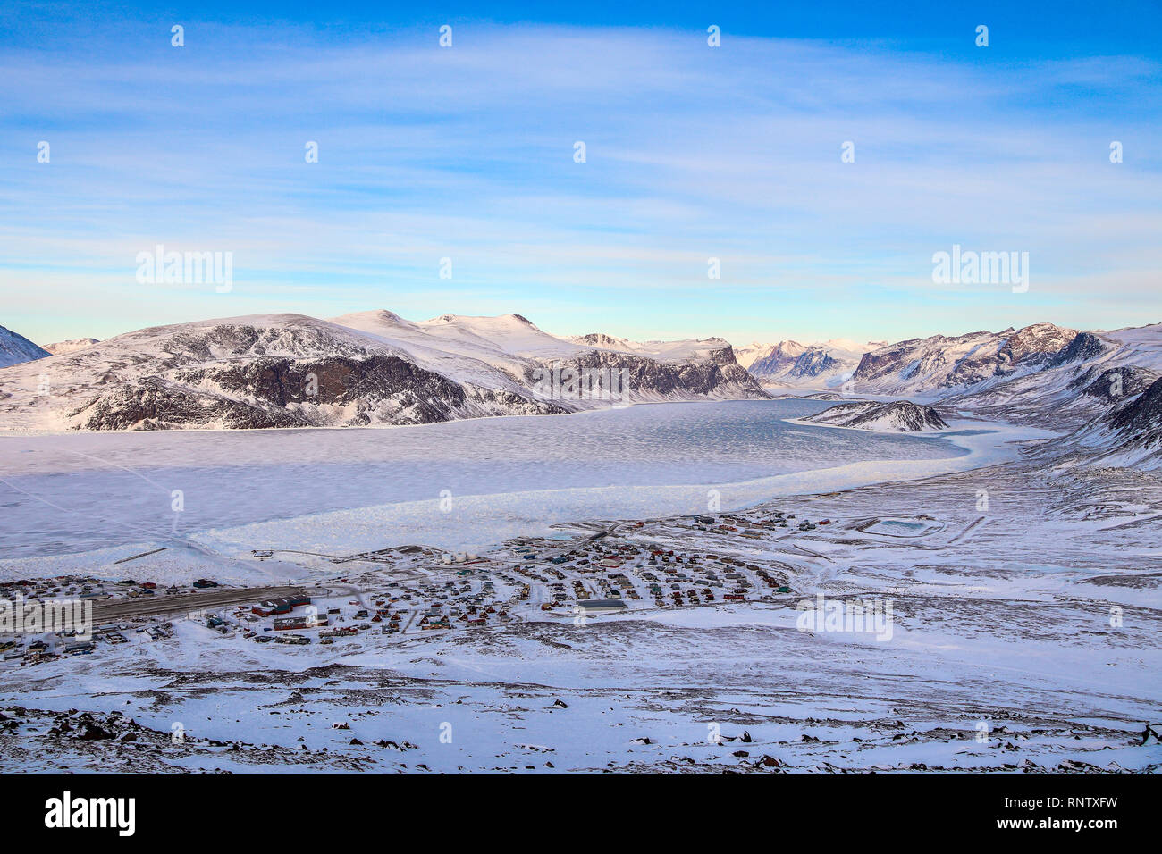 A view of the village of Pangnirtung during winter when the sea has frozen. The fiord leading to Auyuittuq National Park. - Stock Image
