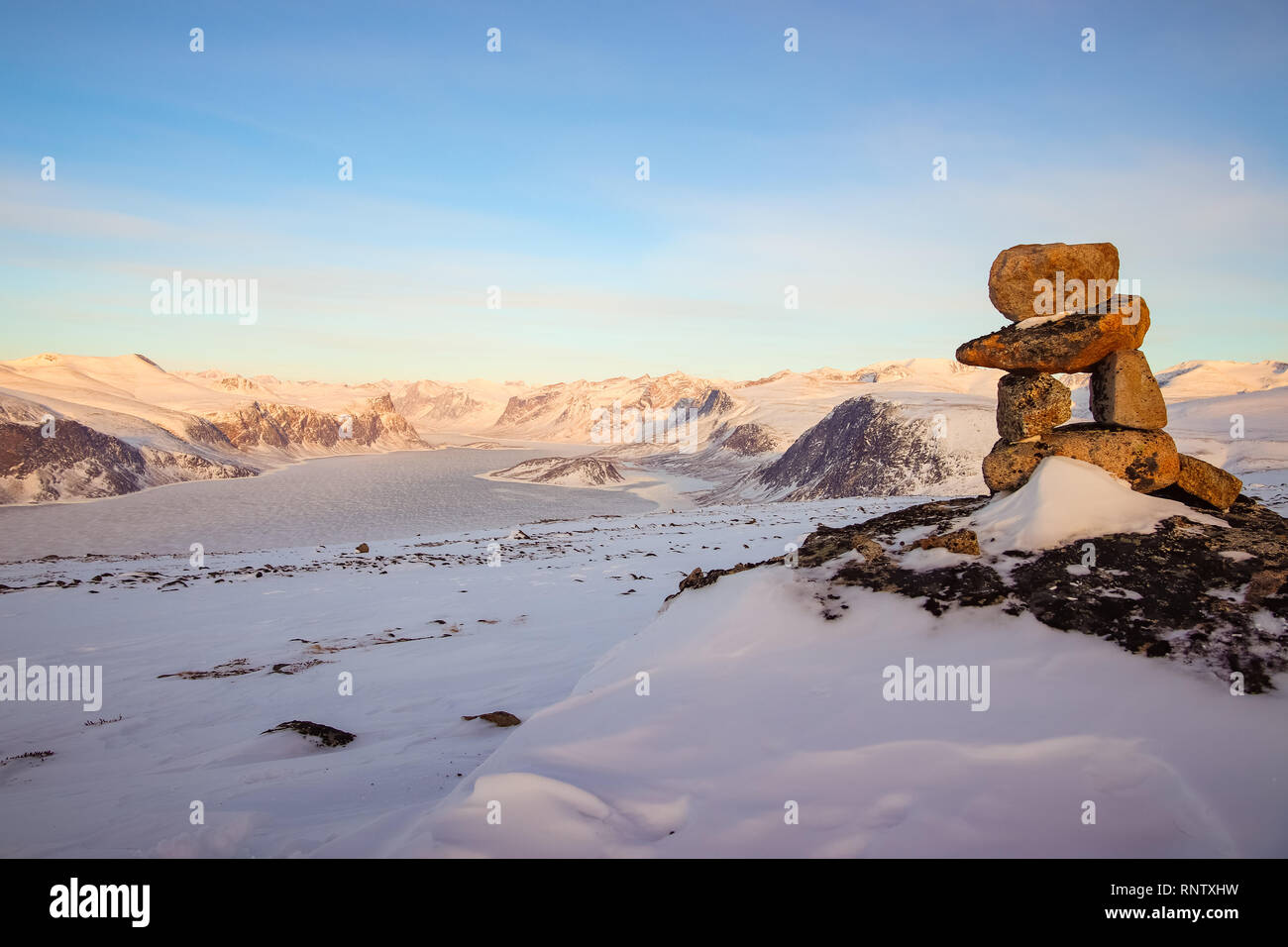 An Inukshuk which is the symbol of Nunavut, located on top of a mountain behind the hamlet of Pangnirtung on Baffin Island. - Stock Image