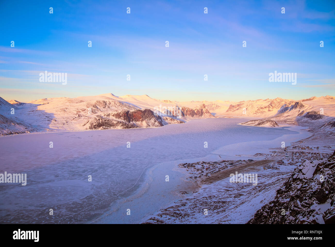 From up in the hills behind Pangnirtung are views over the frozen ice that lead through the fiord on Auyuittuq National Park. - Stock Image