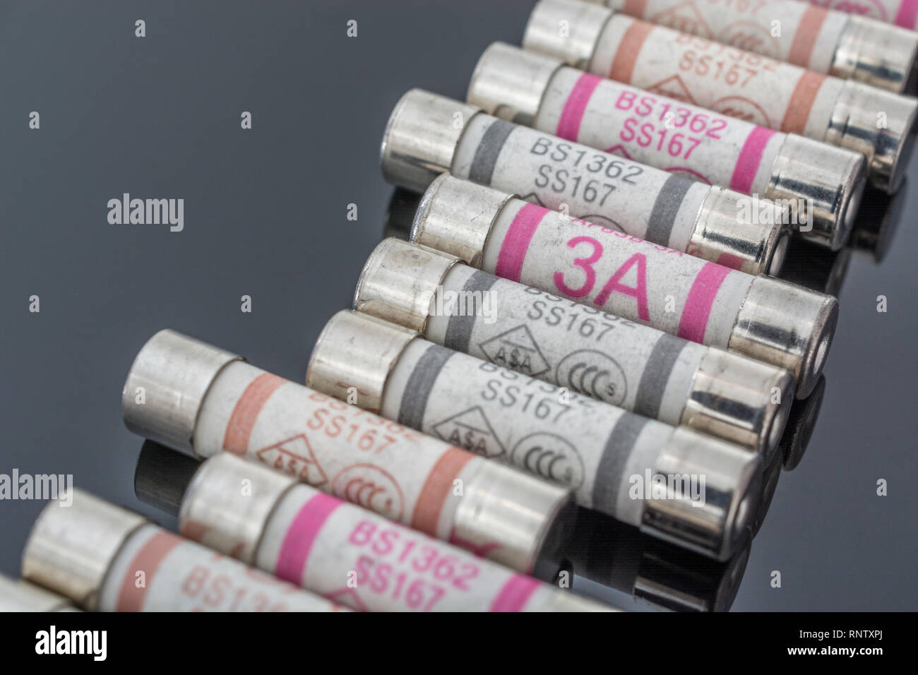 Domestic appliance 3A, 5A & 13A electrical fuses (Ceramic Cartridge type) on reflective black background. Metaphor electrical safety. 25mm L x 6.3mm D Stock Photo