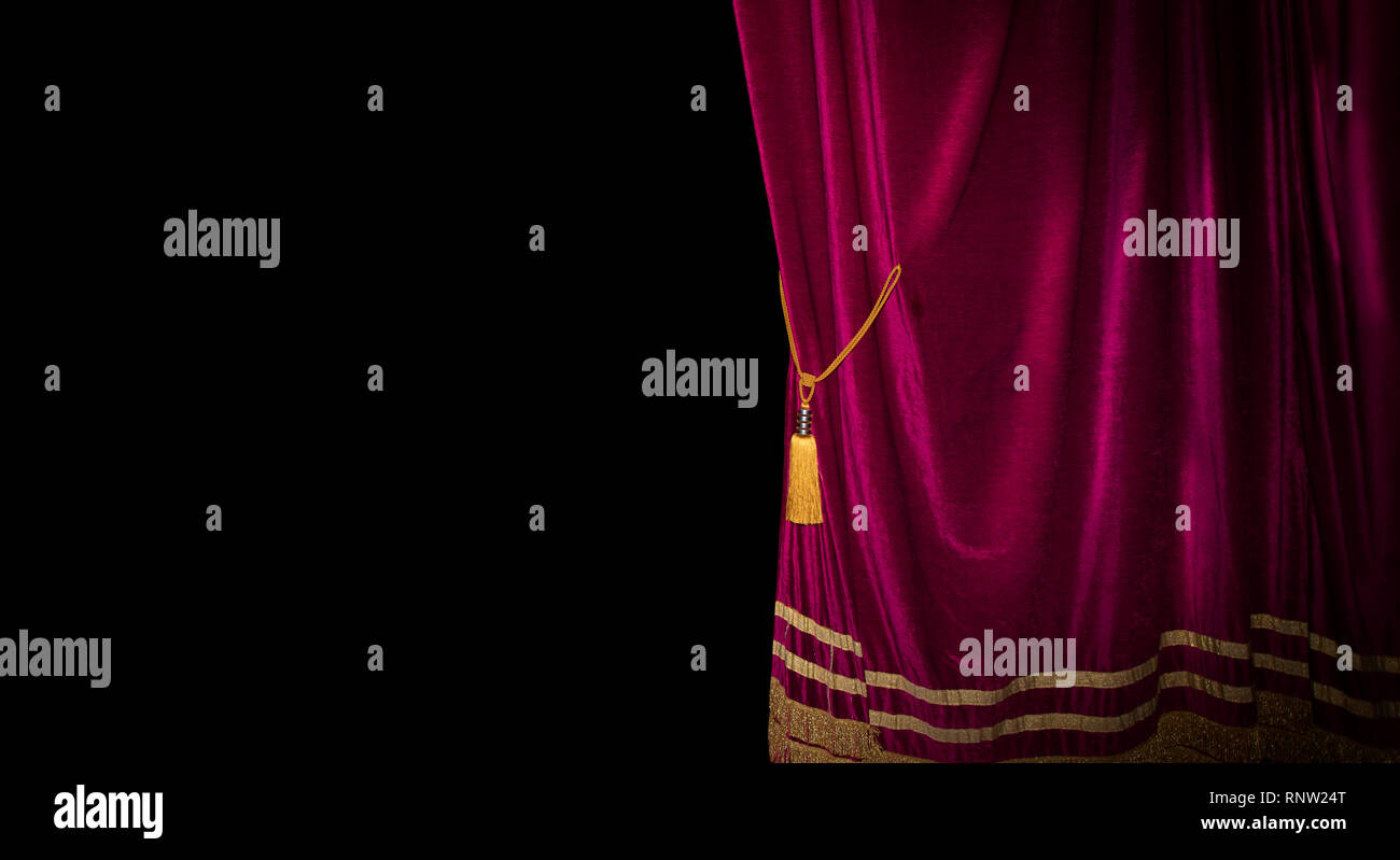 The red curtains are opening for the theater show - Stock Image