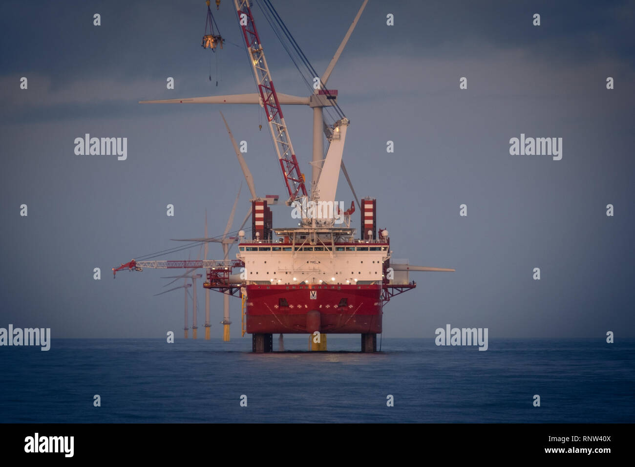 The wind turbine installation and maintenance jack-up vessel conducting maintenance works on London Array Offshore Wind Farm - Stock Image